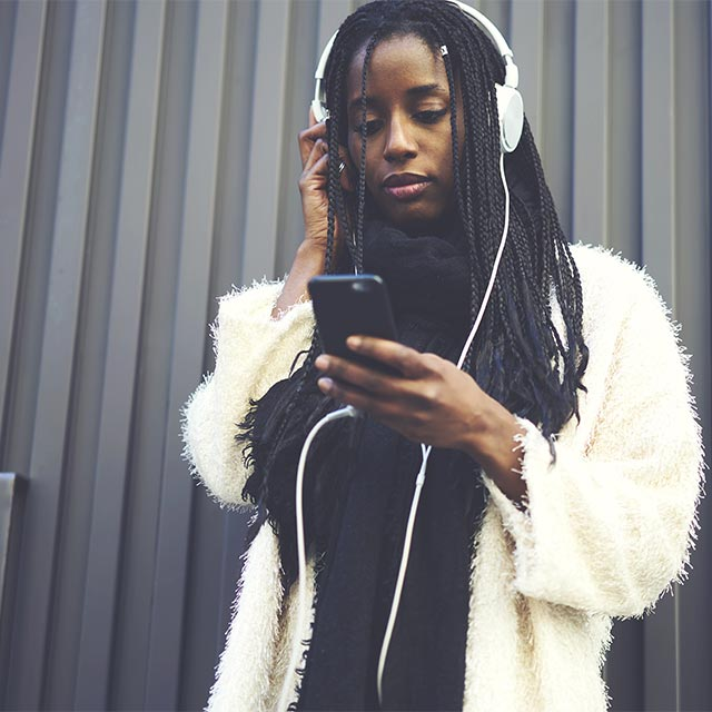 Woman with headphones on looking at smartphone